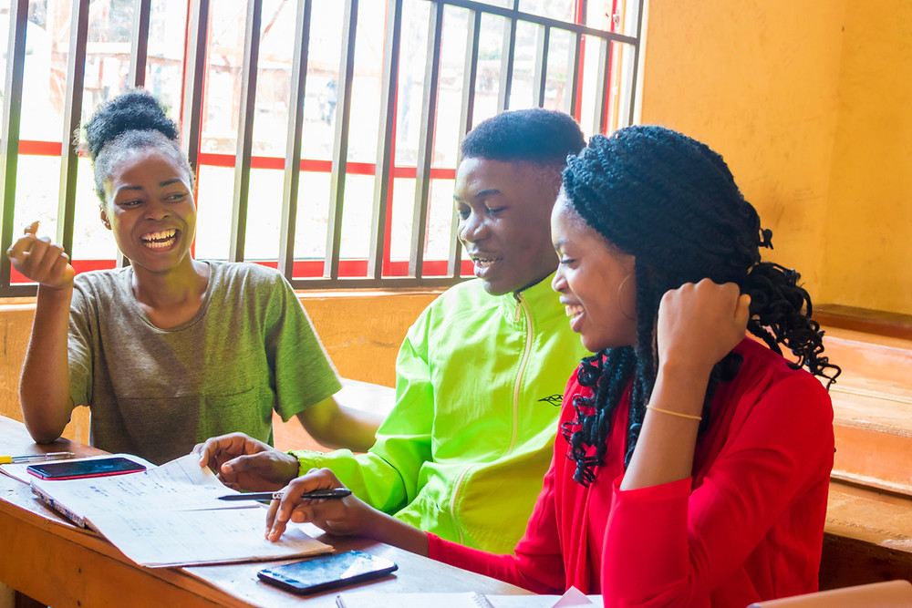 Three African students happily studying together