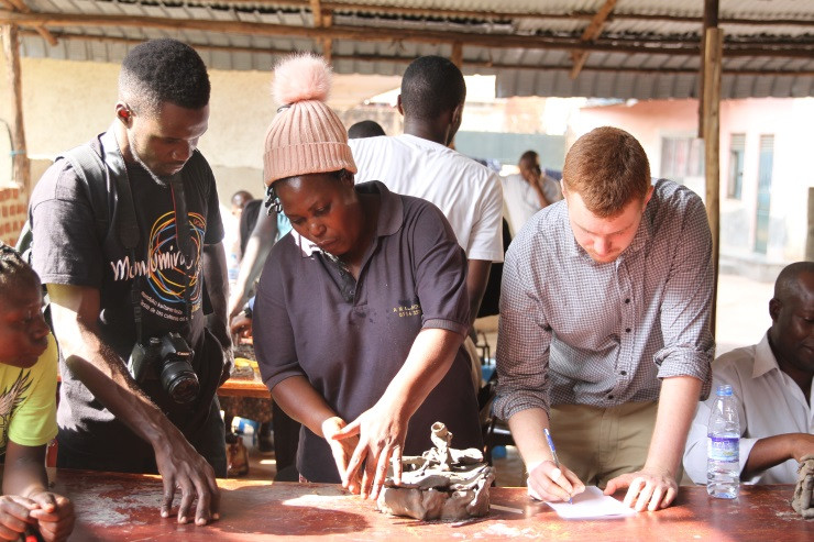 Three people working with clay