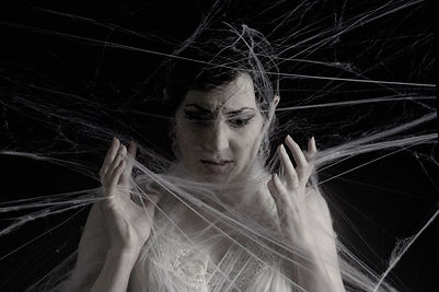 A woman covered in spiders web
