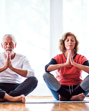 senior-couple-meditating-at-home-PX4QRVD