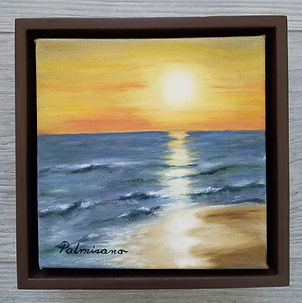 Palmisano_WarmSunset 6x6.jpg framed in a brown floater frame. Warm sunset on ocean water with gentle ripples and a small sand beach area all reflecting the sunset.