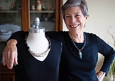 Photo of artist and her mannequin, both wearing necklaces.