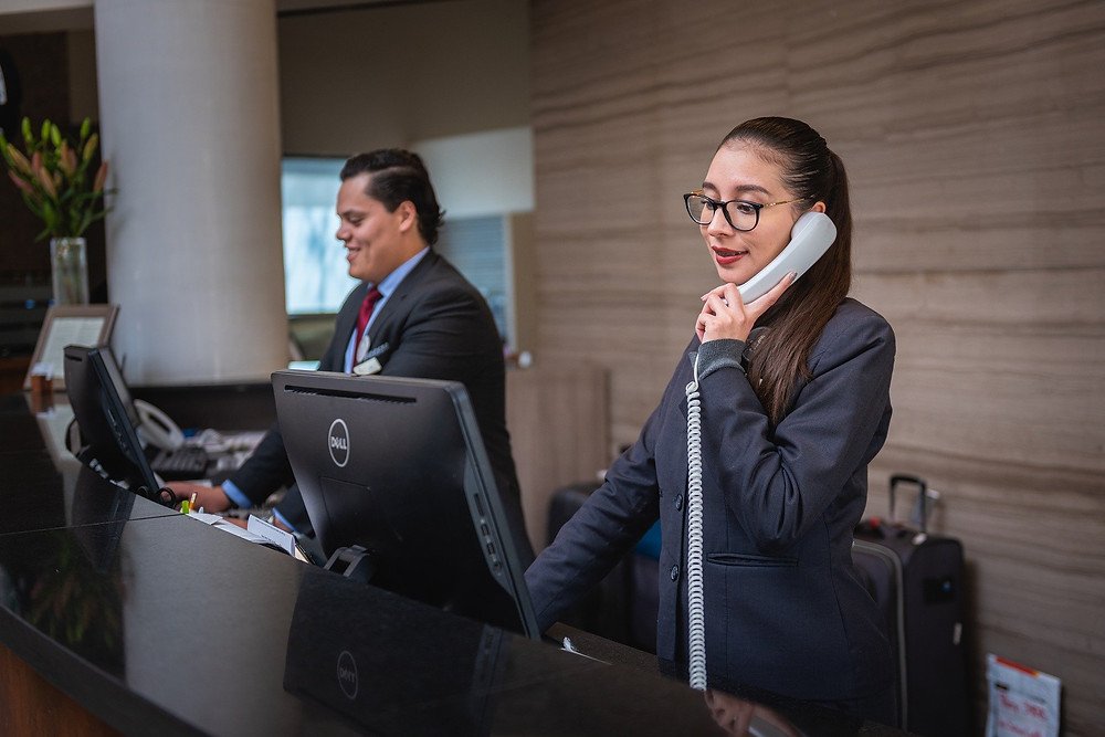 Two hotel workers stand behind a reception desk and take phone calls