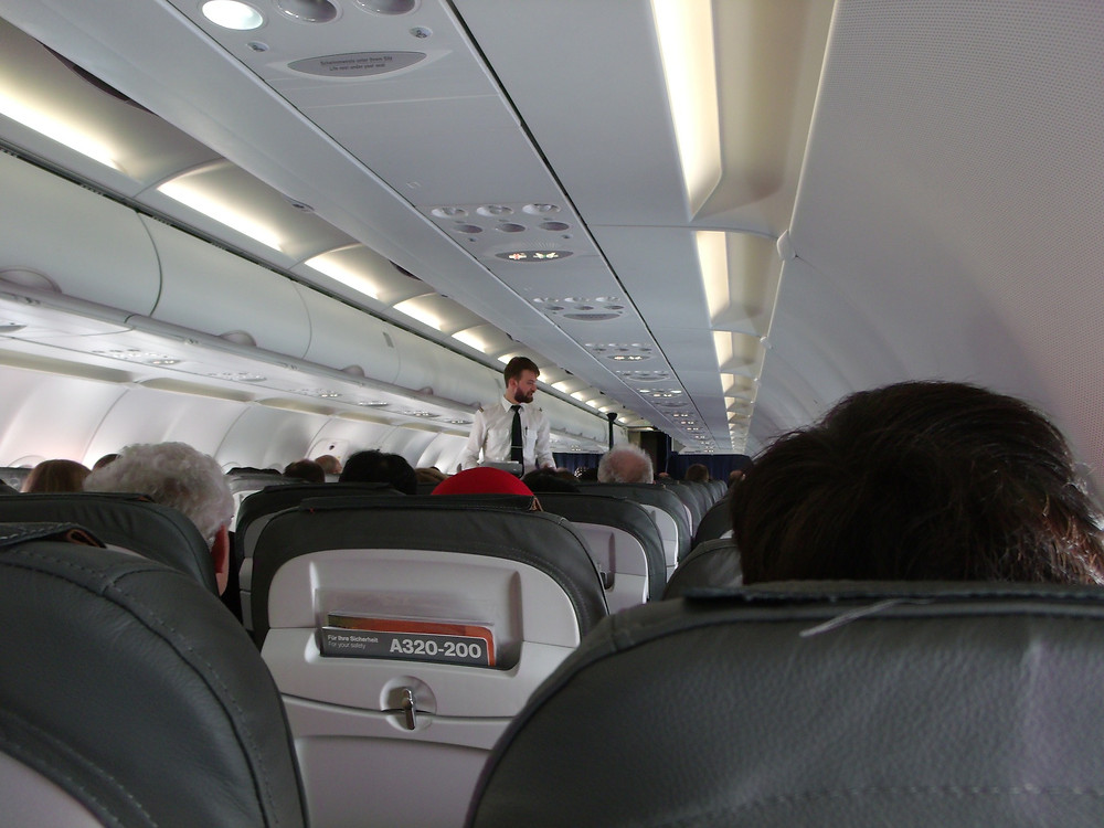 A flight attendant walks down the aisles of an airplane and checks on passengers