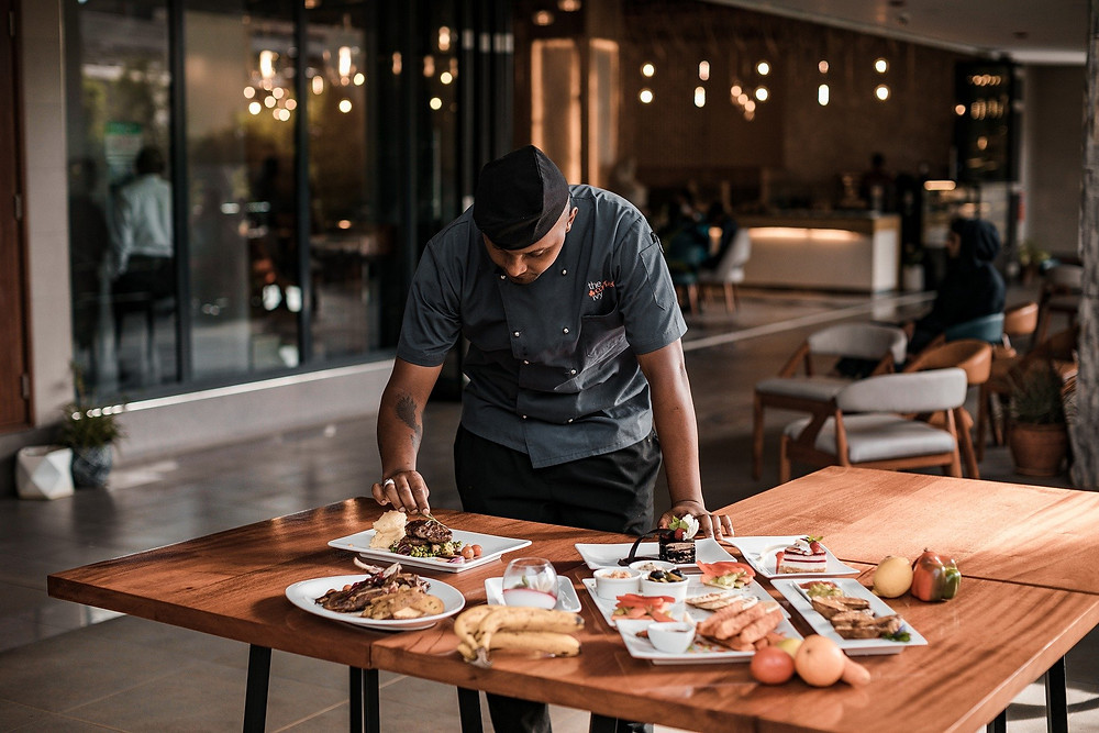 A chef checks the plating of food on a table in a restaurant