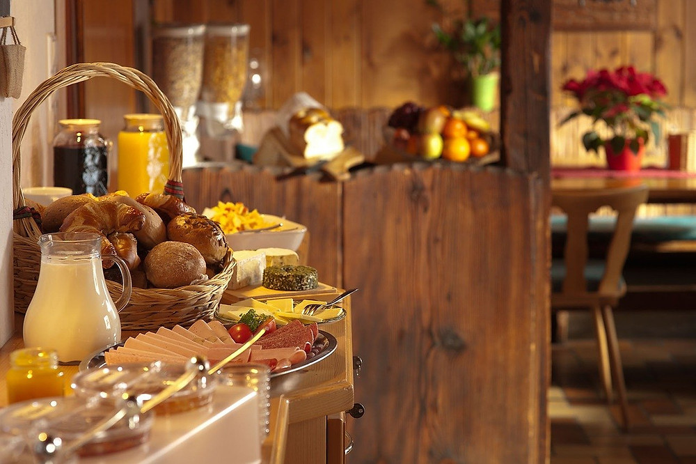 A breakfast buffet table in a hotel, with a basket of croissants and bread