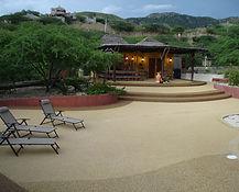 Este es un pavimento decorativo epóxico hecho a base de agregados de cantos rodados de alta dureza y cemento epóxico 100% sólido, con resistencia a la intemperie, antirresbaladizo, lo cual lo hace muy apropiado para áreas de piscinas, bordillos, etc.