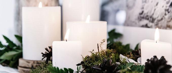 Weiße Kerzen mit Pflanzen Dekor