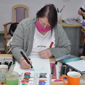 Dragon's Den Sara Davies donates Arts & Crafts materials. The peaceful people put them to good use.