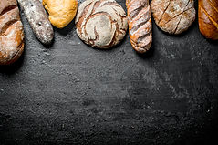 Different kinds of fresh bread. On black
