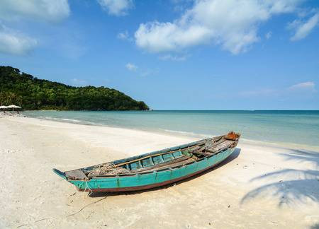 White sand beach with a wooden boat in phu quoc island.