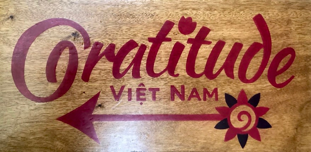 A hand made wooden road-sign for Gratitude Vietnam.