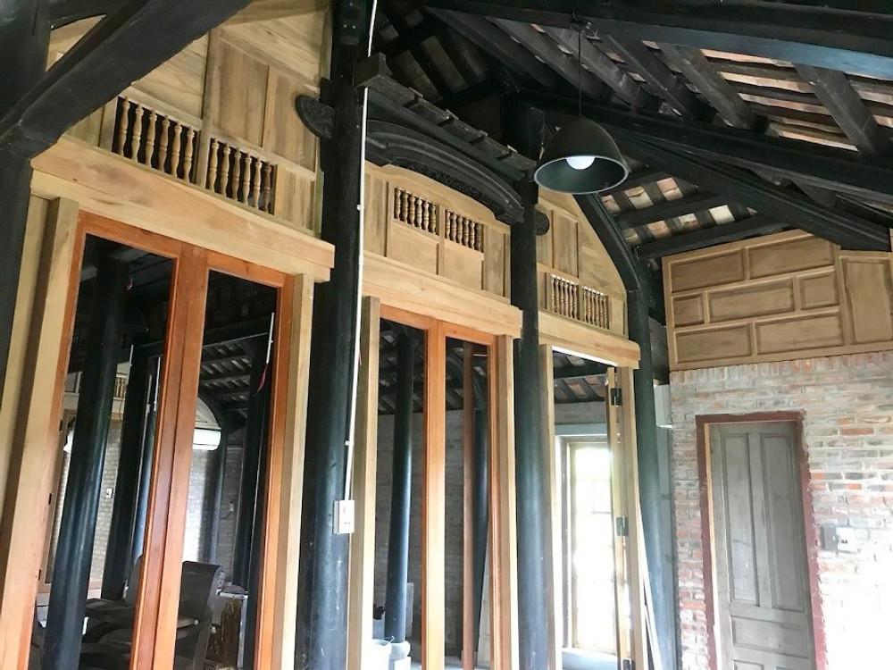 A photograph of a traditional wooden Vietnamese frame with modern carpentry in traditional style for walls.