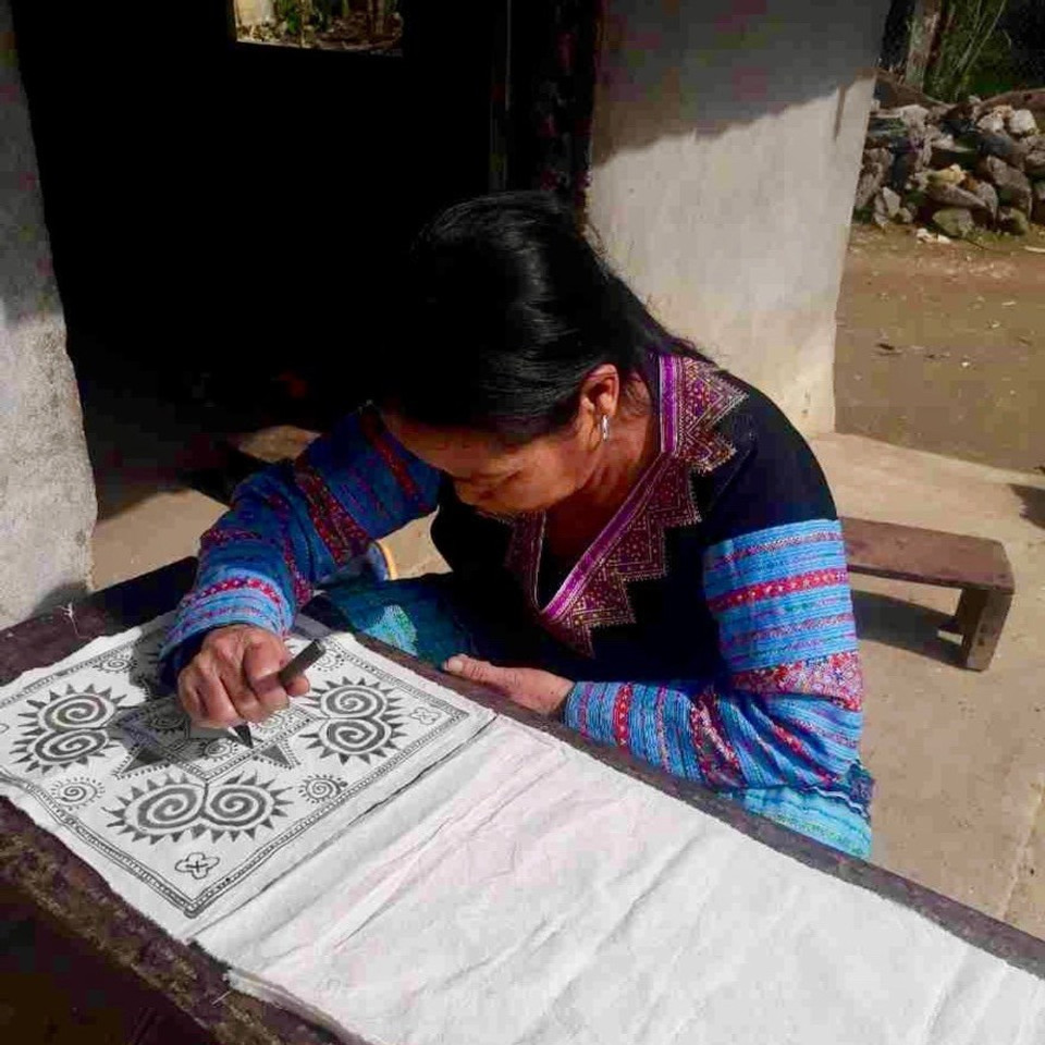 A photograph of a lady from the Hmong People of Hao Binh, stencilling a cushion cover with a traditional story of the elements Earth, Sky, Work and family.