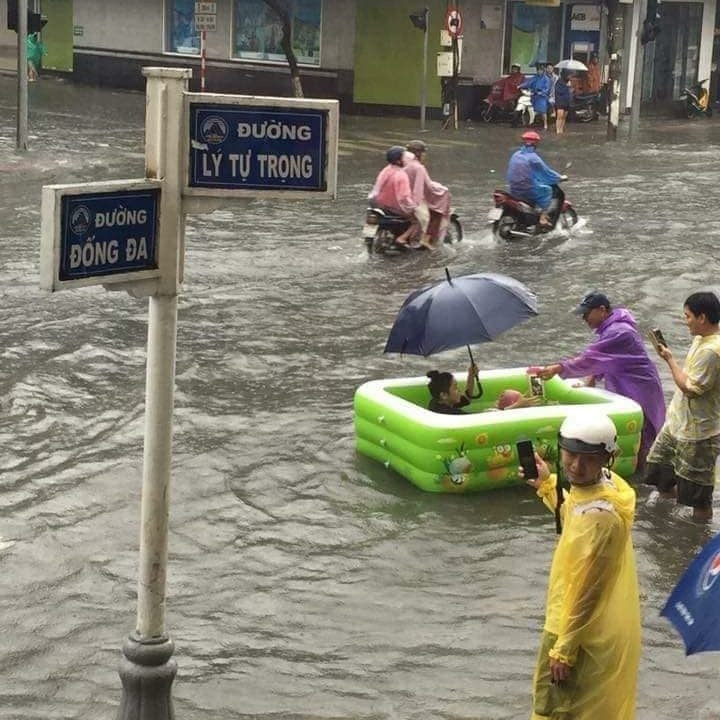 A photograph of people floating along a flooded street in Danang City in a paddling pool!
