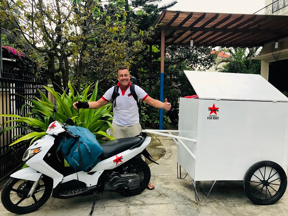 A photograph of Cyril Quynhon, long-time expat in Hoi An with a trailor full of baggage, a bag on his back and another on his bike!