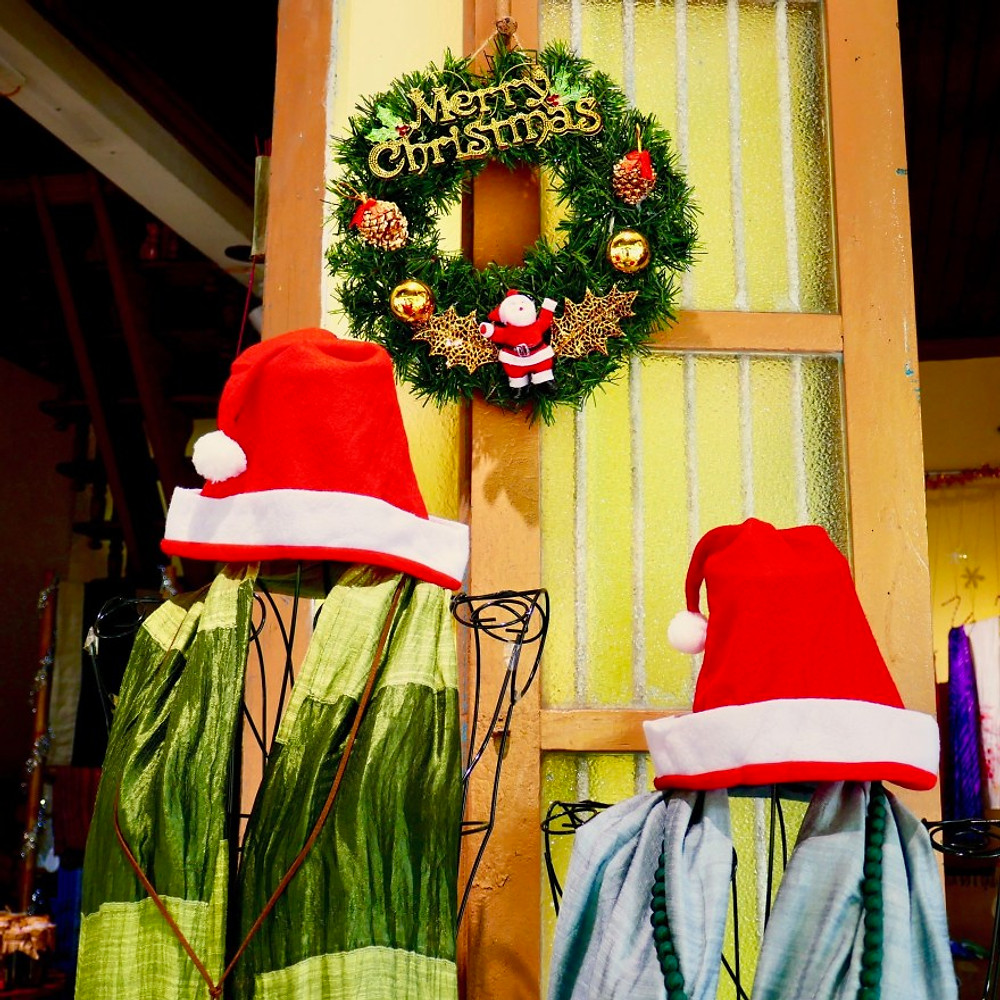 A photograph of a Christmas wreath and two displays of silk scarves and Santa hats on a shop door in Hoi An.