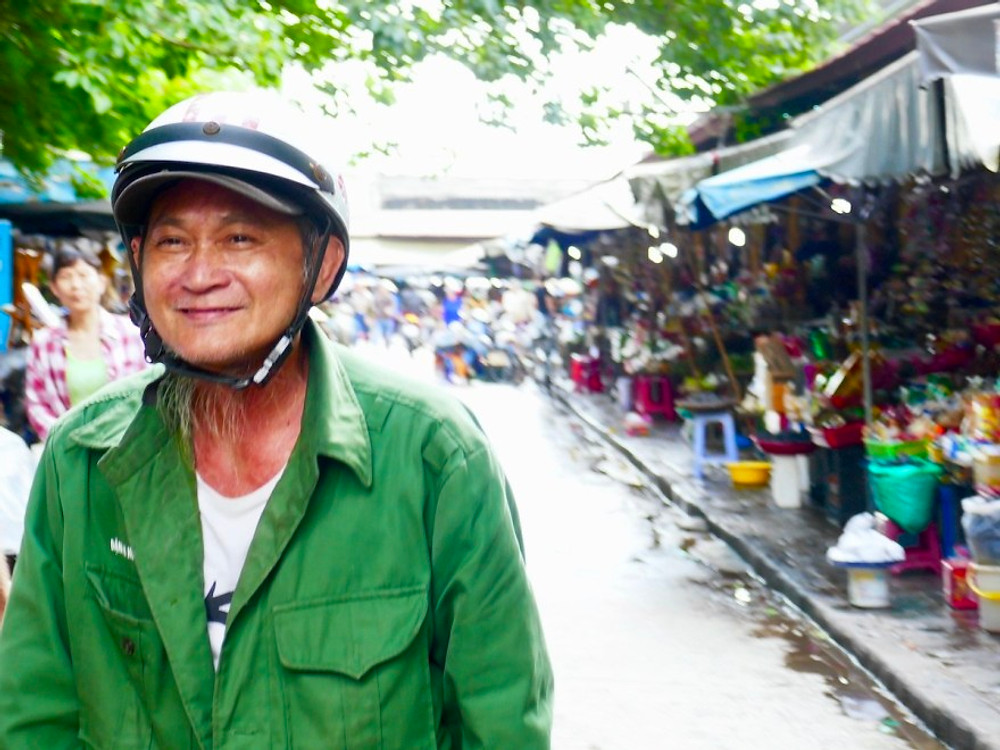 A Vietnamese man is smiling in the street, lined with markets in Hoi An Ancient Town.