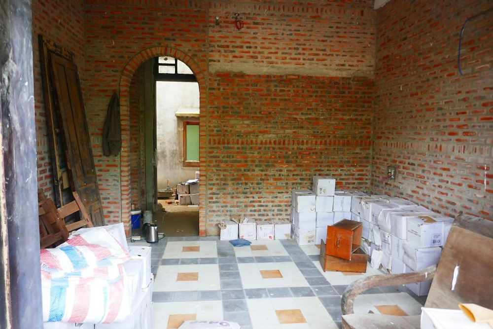 A photograph of a bedroom at Gratitude Vietnam retreat venue and private villa during the early stages of construction. The room has beautiful exposed brickwork and an arched entrance.