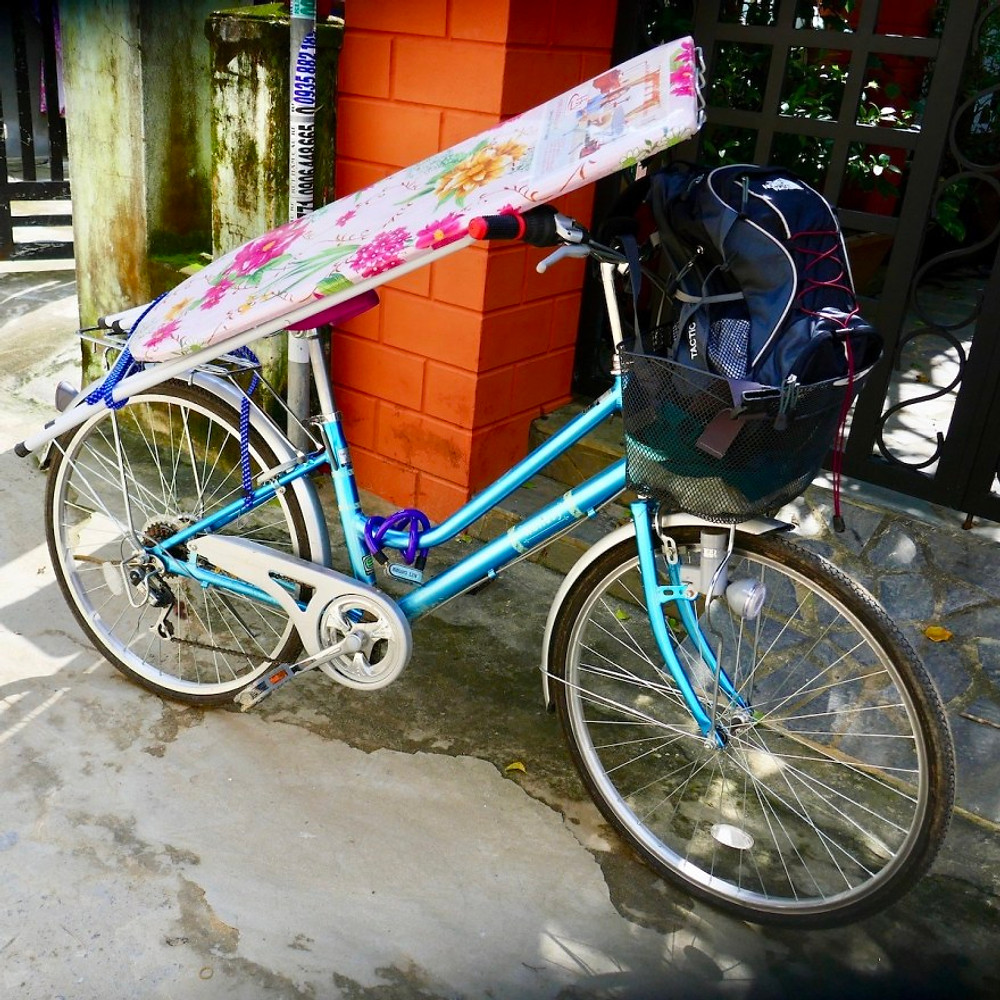 A photograph of a blue bike with an ironing board secured on with bungee elastic.