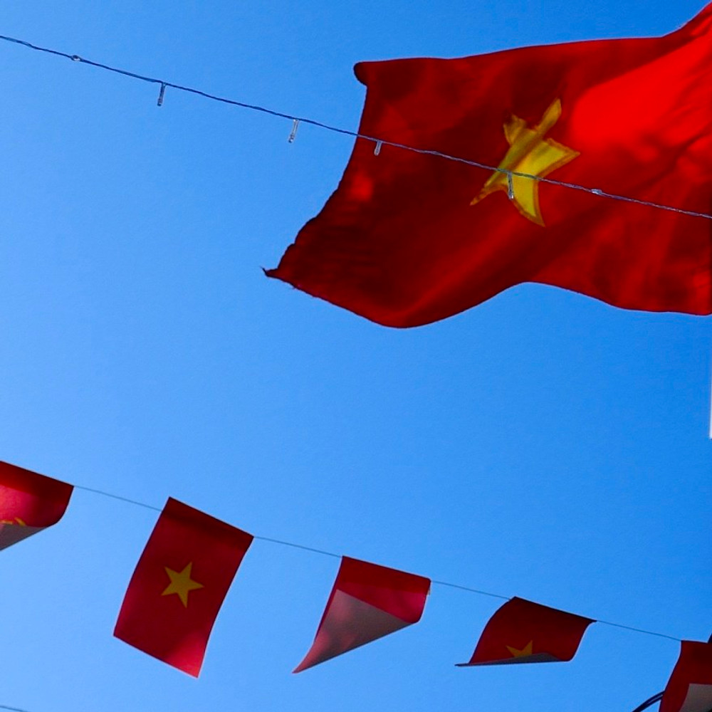 A photograph of the Vietnamese flag against a blue sky with Vietnamese bunting underneath.