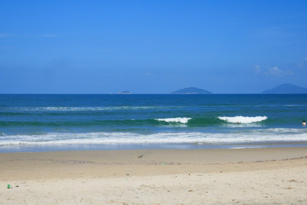 A photograph of the waves rolling on An Bang Beach near the Gratitude Vietnam Retreat Venue.  The sky is a clear blue, the sand powdery and white, and islands are visible on the horizon.