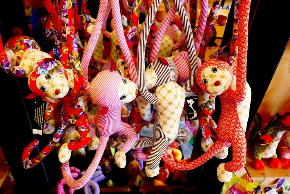 A photograph of hand-stitched, multicoloured, stuffed monkies hanging in a shop in Hoi An
