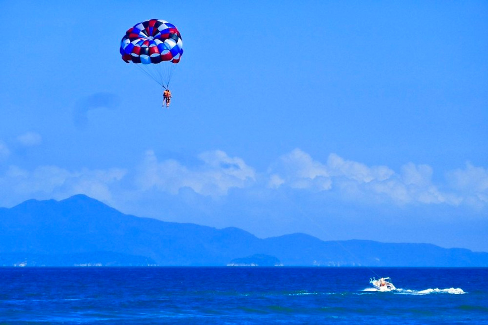 A couple dangling from a parachute as they ascend above the blue ocean next to An Bang beach.