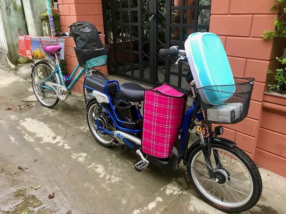 A photograph of an electric bike and pedal bike laden with shopping in Hoi An, Vietnam.