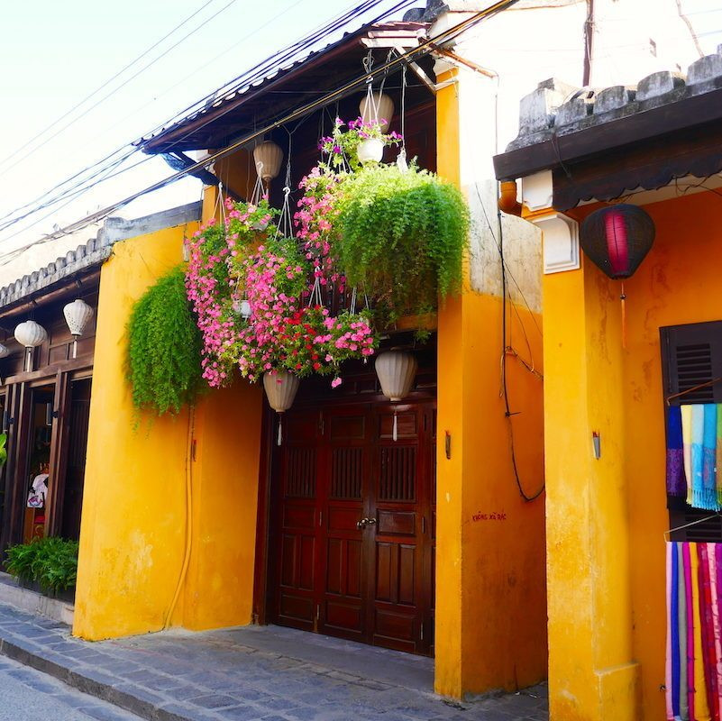 A photograph of a tiny lane set between two traditional houses in the UNESCO world heritage site, Hoi An Old Town. The buildings are painted the traditional mustard yellow and flowers hang from the balcony.