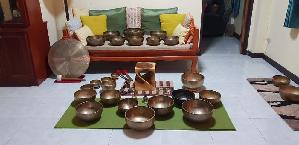 A photograph of many Tibetan Singing Bowls laid out in a living room.