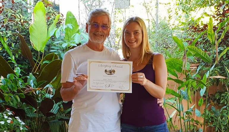 A photograph of Naomi and RJ holding a certificate for sound healing with a garden in the background.