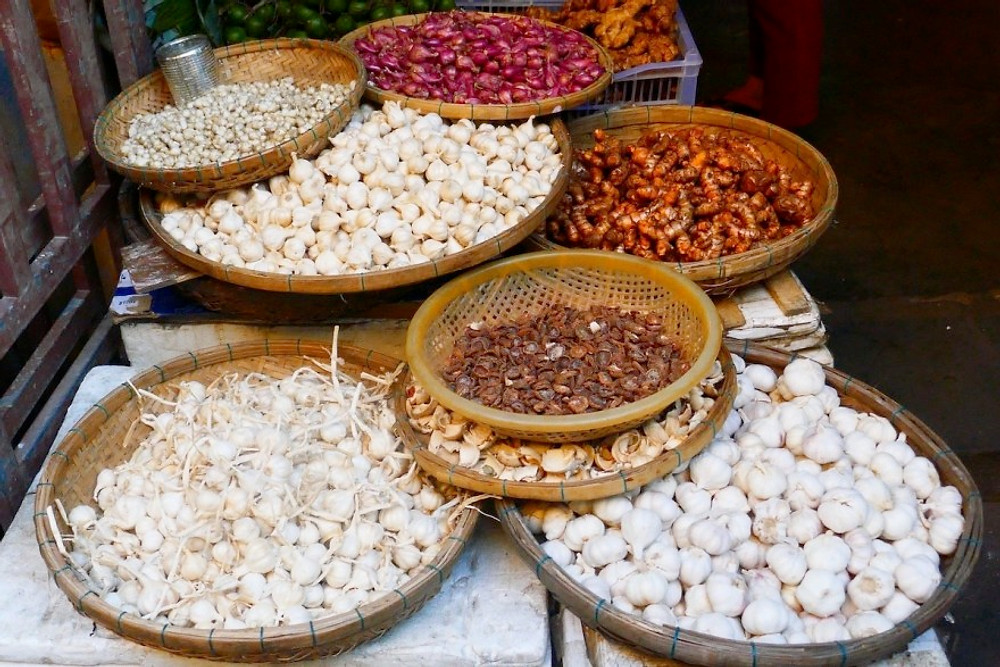 A display of spices in Hoi An market - turmeric, ginger and garlic all sustainable to buy with zero-plastic waste!