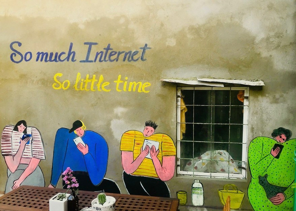 A photograph of a mural in Hoi An with four people painted onto the wall with mobile phones in their hands. The mural reads 'so much internet, so little time.'