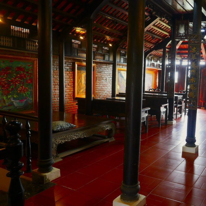 A photograph of an art gallery on Cam Nam Island.  The setting is a traditional Vietnamese wooden structure.  The sunlight gently illuminates the stunning space.