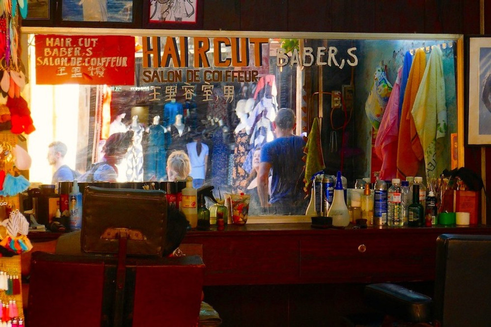 A photograph of the mirror of a traditional barbers in Hoi An. The sign is hand painted and Barbers misspelled B a b e r ' s