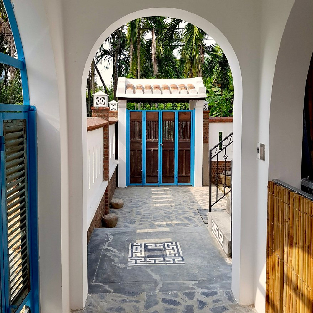 A photograph of the Gratitude Vietnam Villa entrance and reception with upcycled shutters painted a beautiful turquoise.