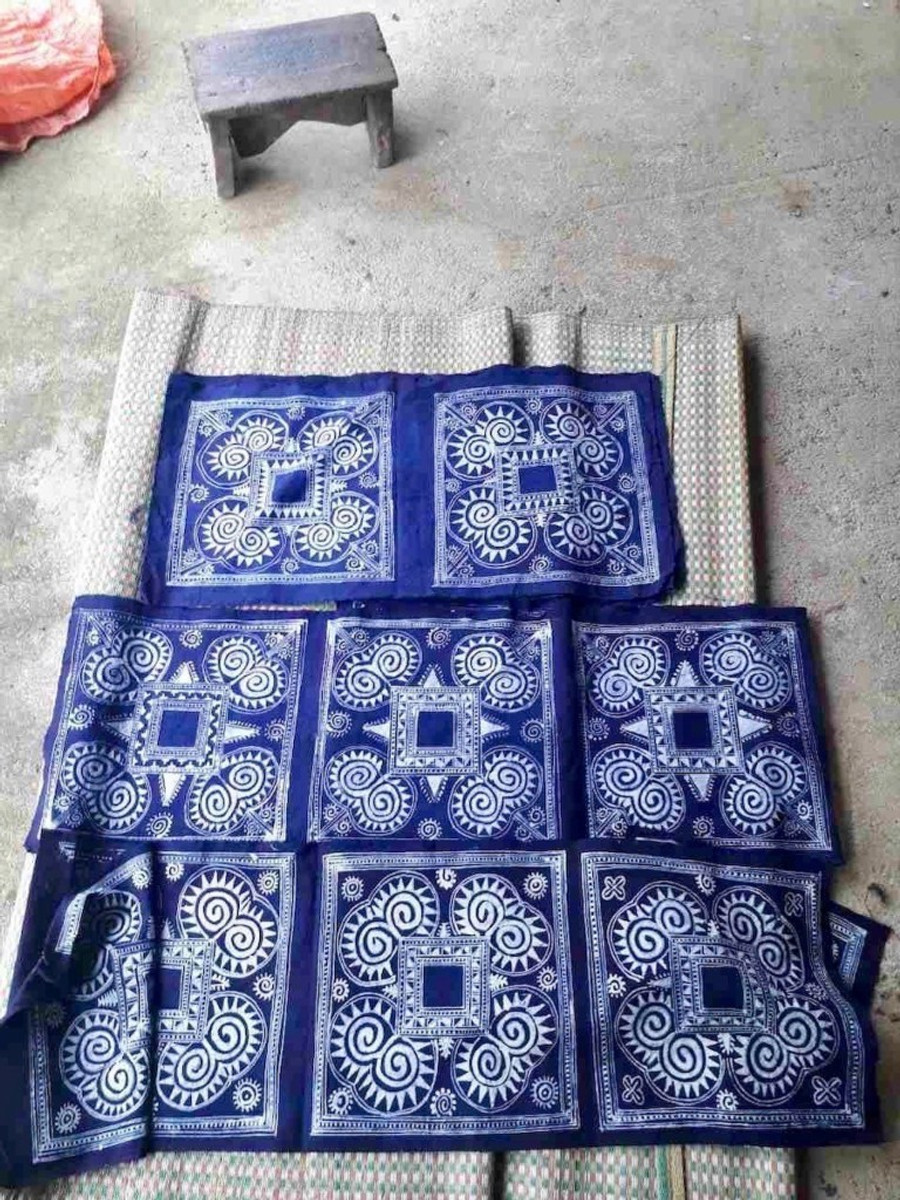 A photograph of traditional Vietnamese Hmong indigo dyed fabric cushion covers in the sun to dry.