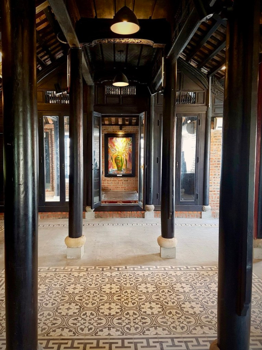 A photograph of the Gratitude Vietnam Villa meditation space. The structure is a traditional wooden house from the Nguyen Dynasty.