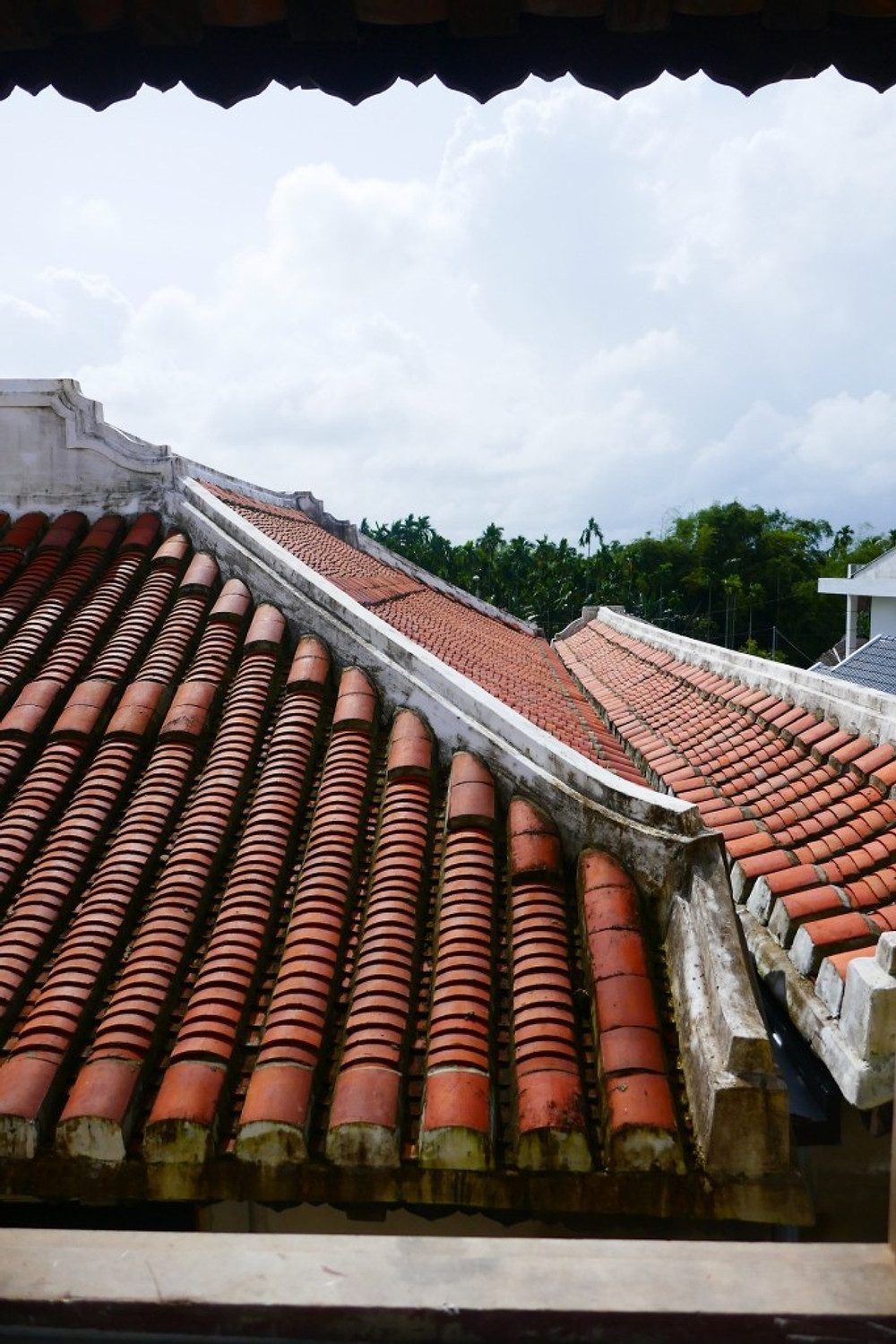 A photograph of a traditional Vietnamese tiled roof, taken from a bedroom at Gratitude Vietnam