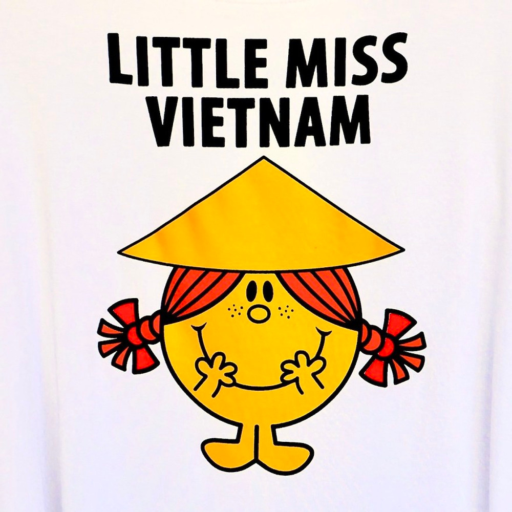 "A white t-shirt with a picture of a girl wearing bunches and a traditional Vietnamese hat. The t-shirt reads ""Little Miss Vietnam""."