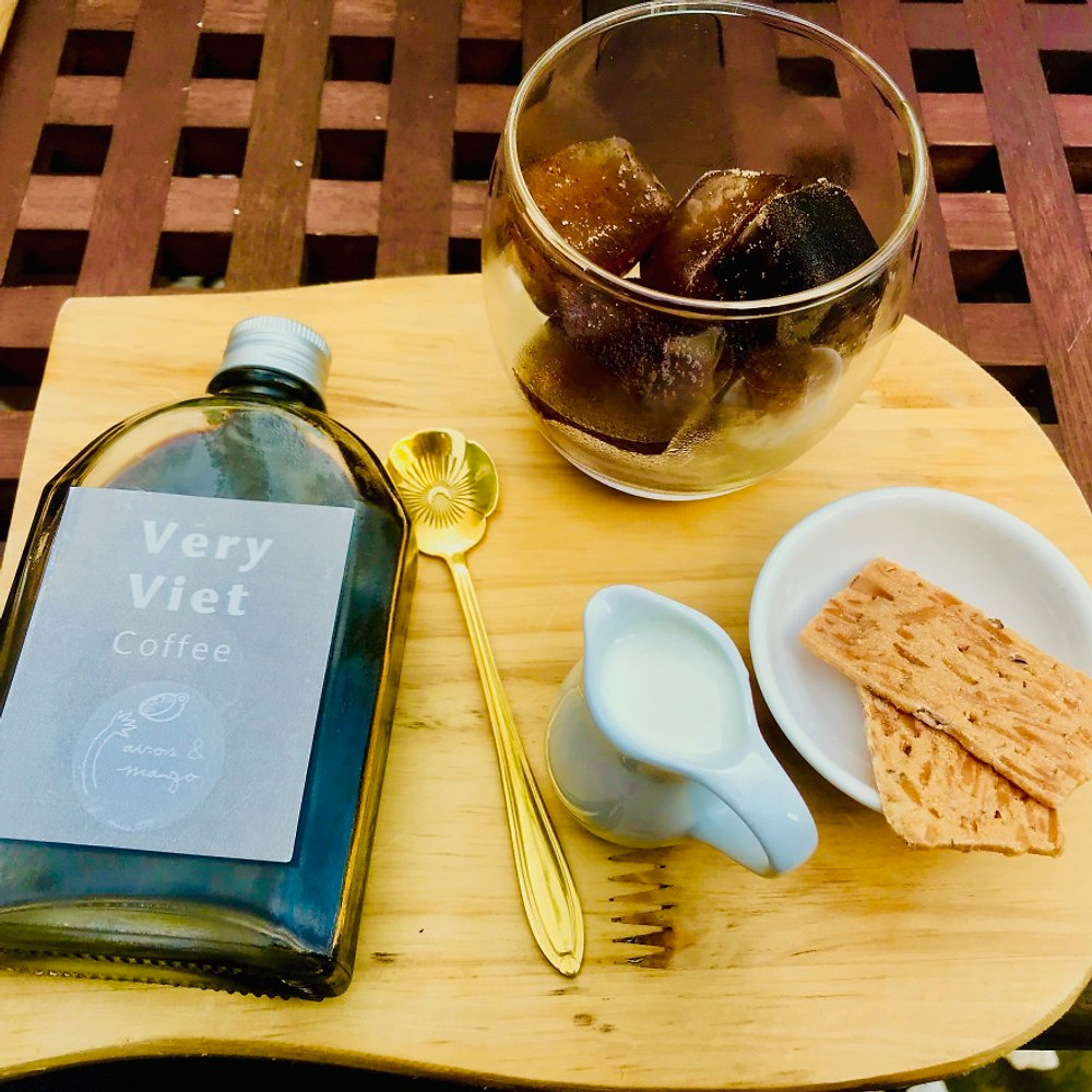 A photograph of Vietnamese coffee in a glass bottle on a wooden tray. The ice-cubes are also coffee and it is served with fresh-milk and a coconut cake!