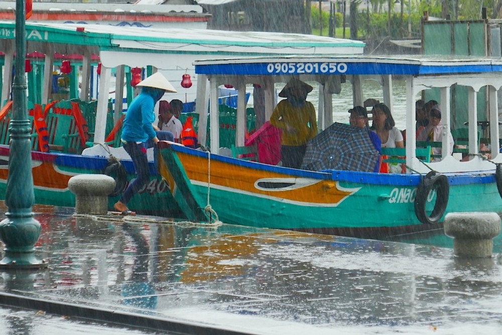 Local people shelter from the rain in a boat, in Hoi An town.
