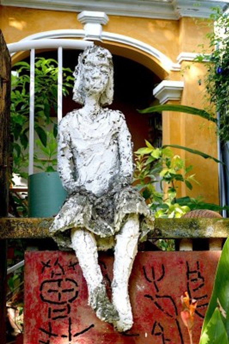 A photograph of a sculpture of a woman sitting atop a wall with a mustard coloured ancient building behind her in Hoi An.