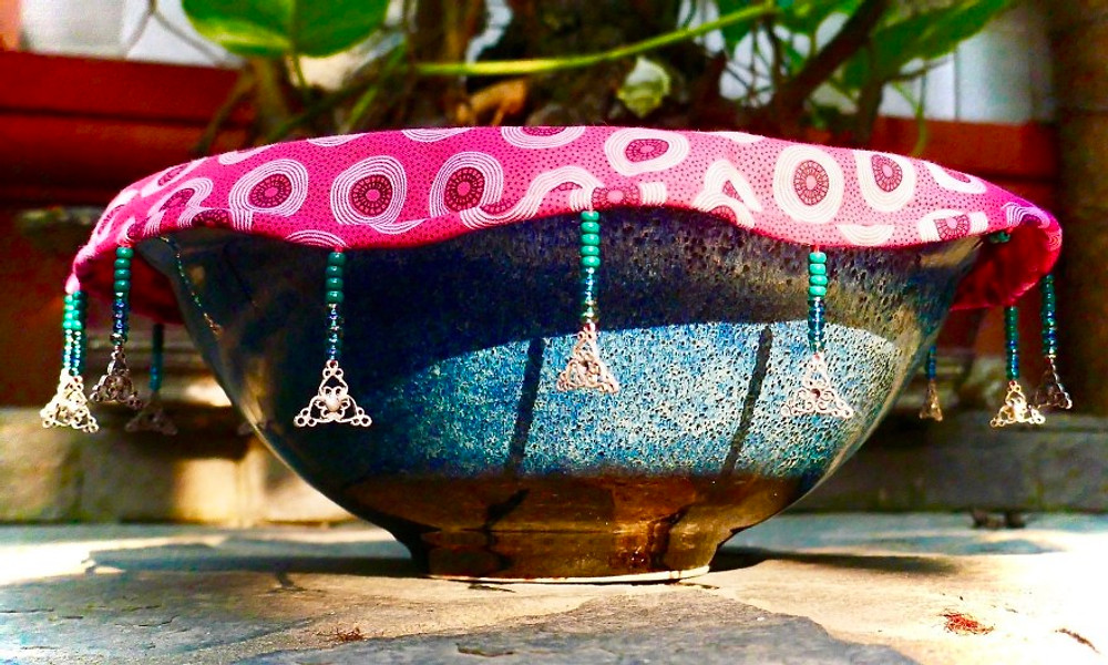 A photograph of a traditional Vietnamese pottery bowl with a fabric, beaded food cover with upcycled beads.