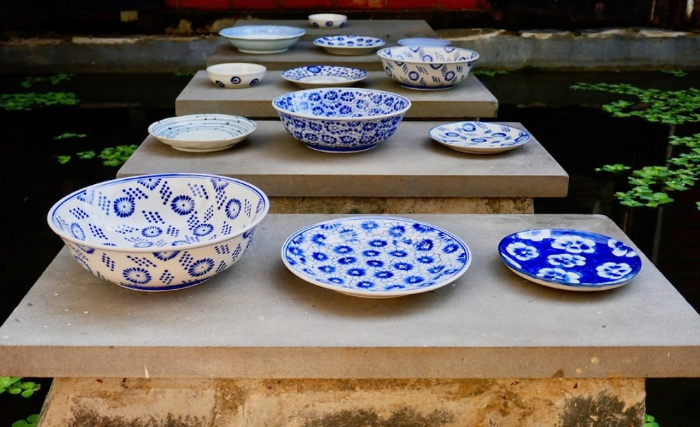 Stunning pre-loved blue and white crockery artfully placed on stepping stones over a pond.