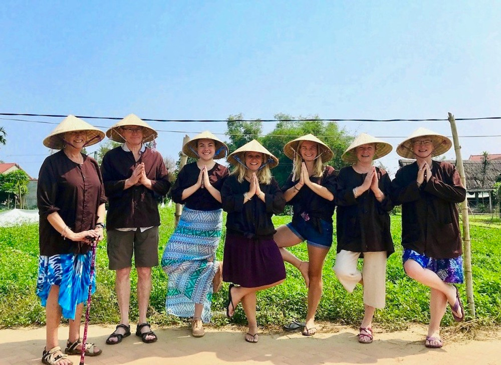 A cheesy photograph of the Gratitude Vietnam family members in Vietnamese hats, striking a tree-pose at Tra Que Vegetable Village, Hoi An.