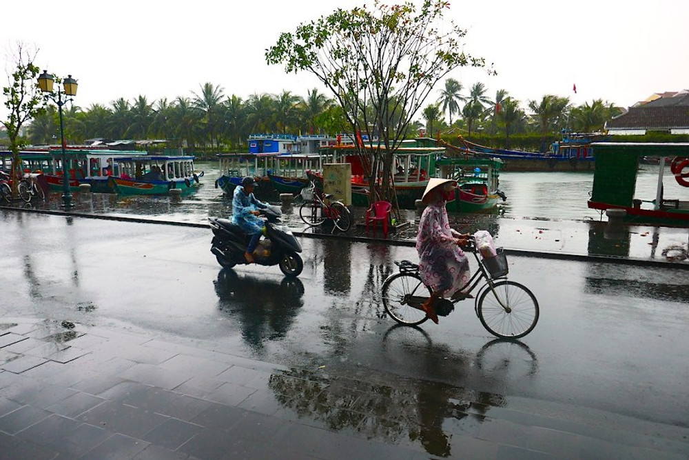 A lady in a traditional hat cycles through the rain in Hoi An Old town. The River Thu Bon is in the background.
