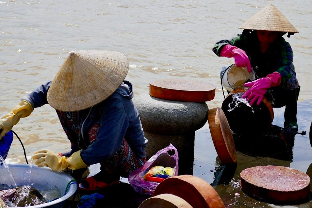 Two women clean fish at the riverside in Hoi An Old Town. They are wearing Vietnamese hats and coloured rubber gloves!