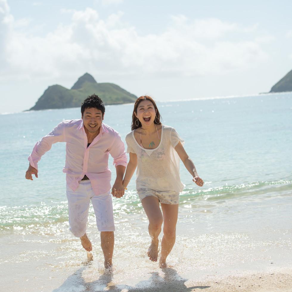 Couple running on Lanikai Beach, Oahu